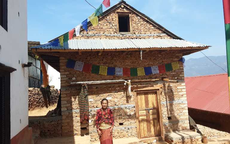 an elderly in front of her newly built house.